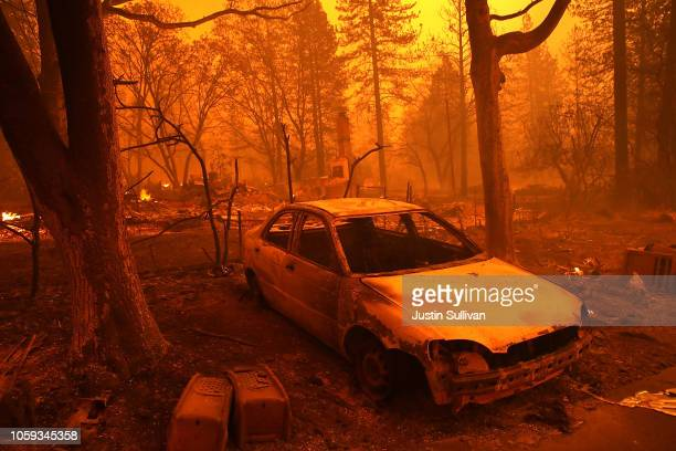 Burned out car sits in front of a home that burned as the Camp Fire moves through the area on November 8, 2018 in Paradise, California. Fueled by...
