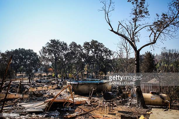 TOPSHOT Burned residences vehicles and a pool line a fireravaged neighborhood after the Clayton Fire burned through Lower Lake California on August...