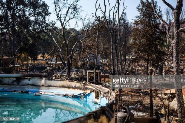 Burned residences vehicles and a pool line a fireravaged neighborhood after the Clayton Fire burned through Lower Lake California on August 16 2016 A...