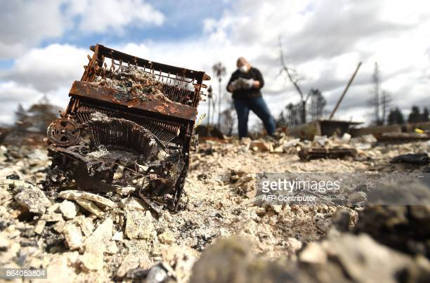 A burned typewriter sticks out of burned ashes as Josette Lushenko searches through remains where her sister Karen Aycock died during the fire in the...