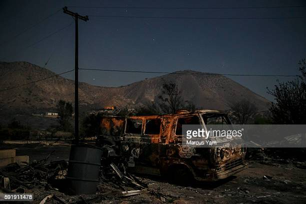 A burned van sits on a land alongside Highway 138 as the Blue Cut fire continues to ravage San Bernardino County Calif on Aug 18 2016