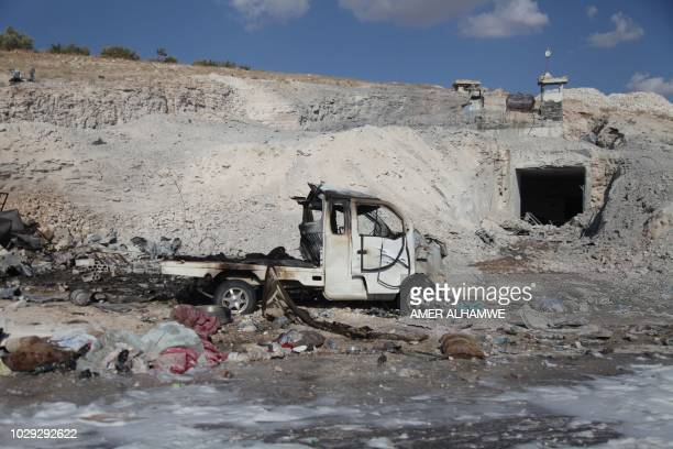 A burned vehicle and personal belongings are seen at a site in Hass town after an airstrike by proregime forces on the south of Idlib province on...