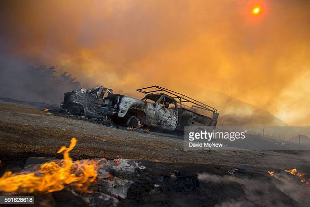 Burned vehicles are seen on a country road at the Blue Cut Fire on August 17 2016 near Wrightwood California An unknown number of homes and...