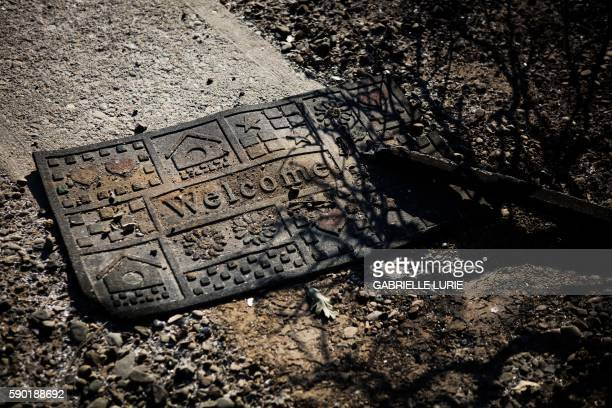 A burned welcome mat can be seen in the remains of a home which was destroyed after the Clayton Fire burned through Lower Lake California on August...