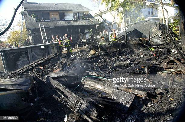 Burned wreckage of American Airlines flight 587 lies in the back yard of a house after it crashed in the Rockaway section of Queens