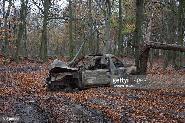 A burnedout car found abandoned by unknown vandals on 27th November 2016 in woodland near Hollingbourne Kent England Flytipping of industrial and...
