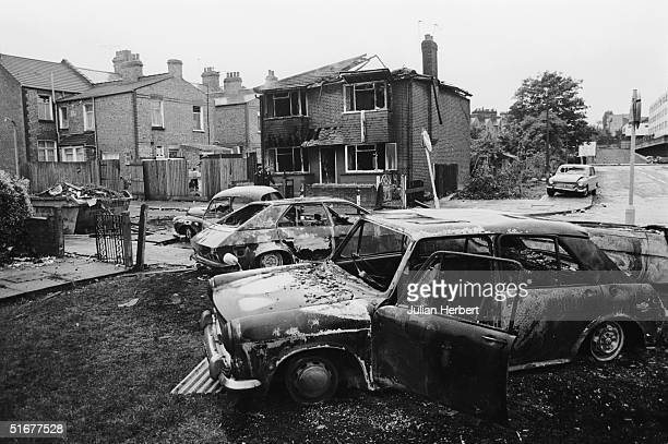 A burnedout house and cars on the Broadwater Farm housing estate Tottenham London the day after the riot of 6th October 1985