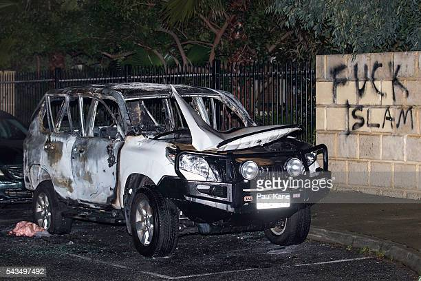 A burnedout Toyota 4WD vehicle and graffiti are seen on Tonbridge Way after a suspected fire bombing outside the Thornllie Australian Islamic College...