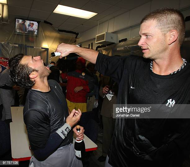 J Burnett of the New York Yankees pours champagne into the mouth of Nick Swisher after a win over the Minnesota Twins in Game Three of the ALDS...