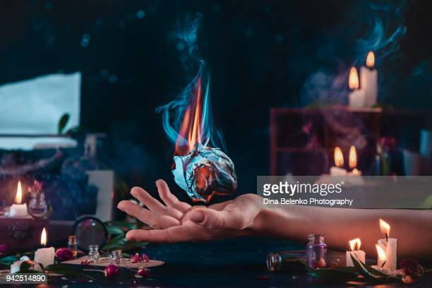 burning ball of crumpled paper on a writer hand. dark fantasy still life with candles, typewriter and open fire. - paranormal stock pictures, royalty-free photos & images