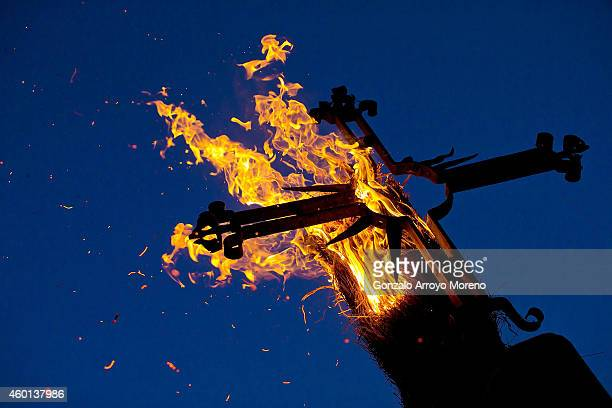A burning broom fires lied on a crucifix at Constitution Square during the 'Los Escobazos' Festivial on December 7 2014 in Jarandilla de la Vera...