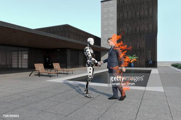 Burning businessman handshaking with cyborg