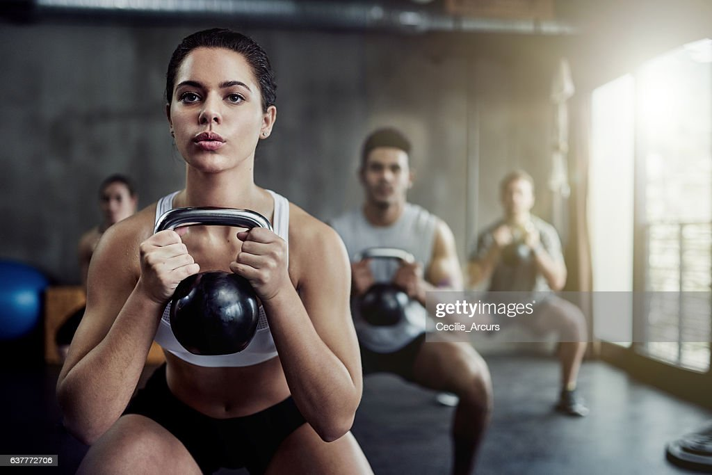 Burning calories and strengthening her core with a kettlebell : Stock-Foto