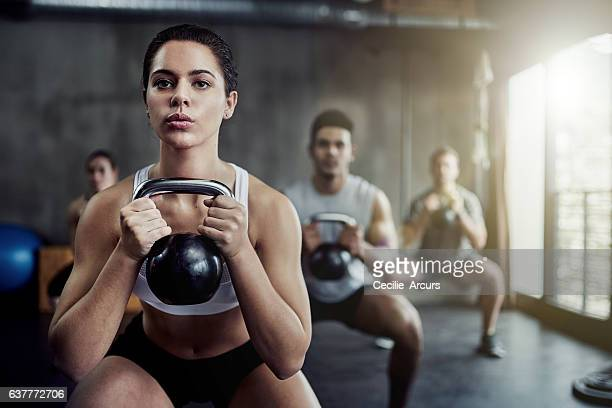 burning calories and strengthening her core with a kettlebell - bodybuilding stockfoto's en -beelden