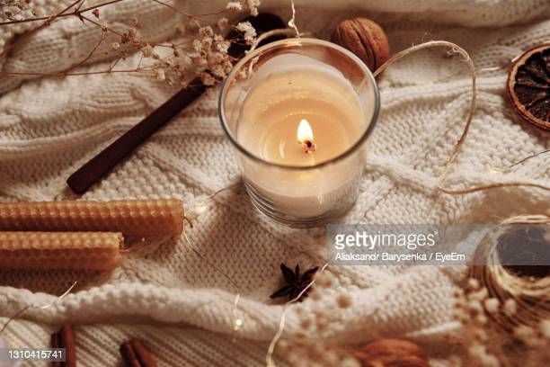 burning candle and christmas decoration, top view. winter cozy home and hygge concept - candle stock pictures, royalty-free photos & images
