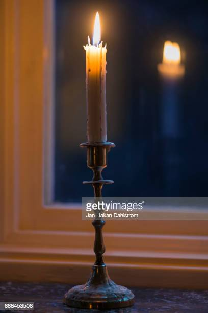 Burning candle in window