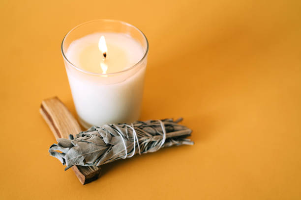 Burning candle, Palo Santo sticks and White Sage on yellow background. Set for aromatherapy and rituals. Copy space for your design. Top view