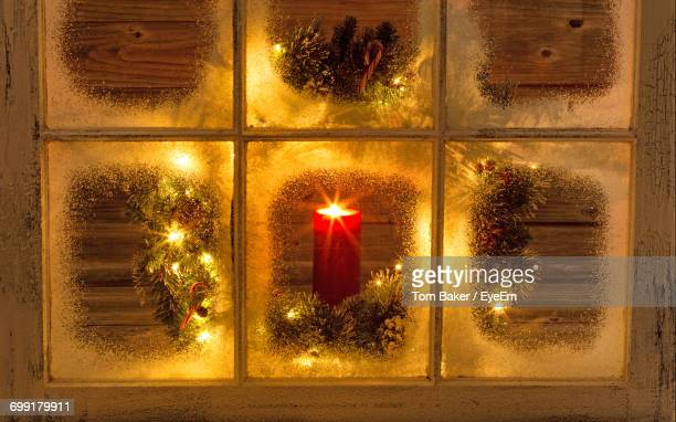 Burning Candle With Christmas Wreath Seen Through Frosted Glass Window