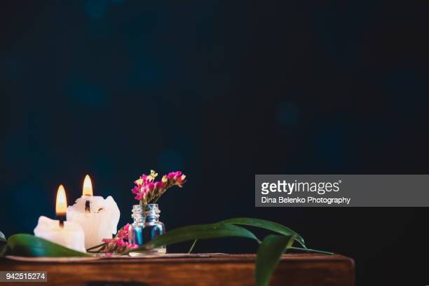 Burning candles and a glass bottle with tiny purple flowers on a dark background. Dark botany still life with copy space.