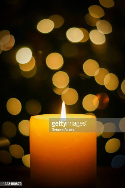 burning candles in from to out of focus holiday lights - christmas decore candle stock pictures, royalty-free photos & images