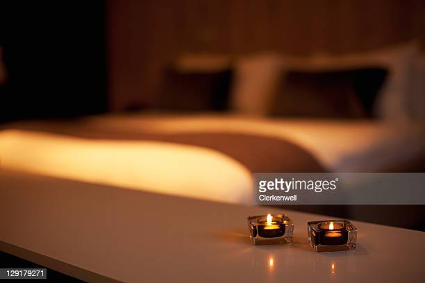 burning candles with luxurious bed in the background - candle light stock pictures, royalty-free photos & images