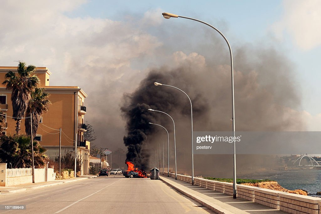 Burning car in the street of sicilian town. : Stock Photo