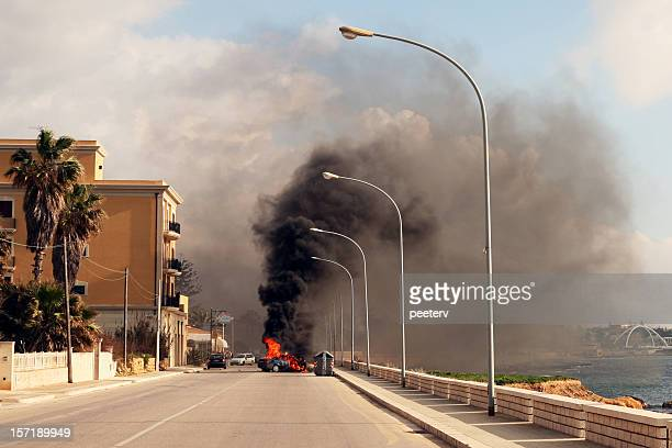 Burning car in the street of sicilian town.