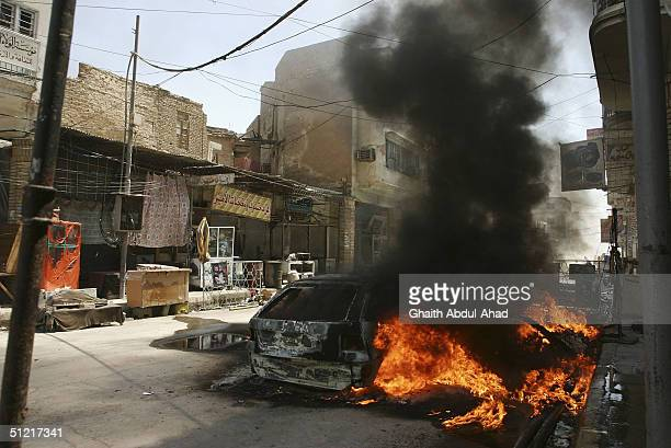 A burning car is seen 50 meters away from the shrine of Imam Ali on August 25 2004 in Najaf Iraq The car was hit by US fire in the Rassol street the...