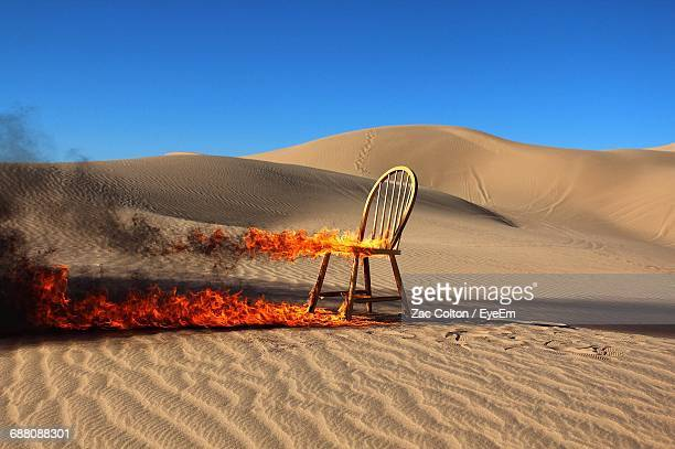 burning chair in desert against clear blue sky - burning stock pictures, royalty-free photos & images