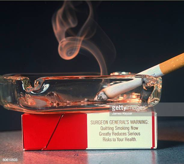 Burning cigarette in ashtray resting on pack of Marlboro cigarettes w Surgeon Gen's Warning on side