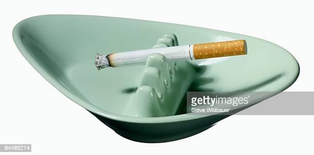 Burning cigarette in green ashtray on white