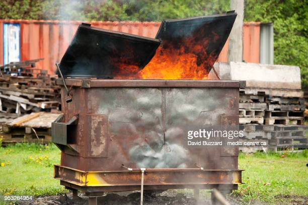 a burning dumpster fire, as part of a fire fighter's training exercise.  squamish bc, canada.  april 29, 2018. - garbage bin stock pictures, royalty-free photos & images