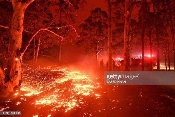 TOPSHOT Burning embers cover the ground as firefighters battle against bushfires around the town of Nowra in the Australian state of New South Wales...