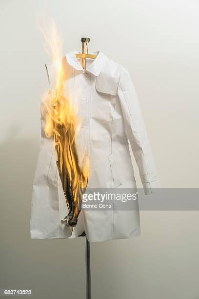 Burning fashion sample pattern against wall in design studio
