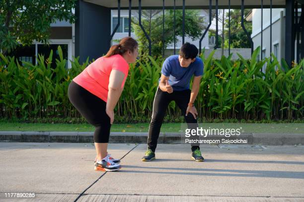 burning fat outdoors - skinny man fat woman stock pictures, royalty-free photos & images