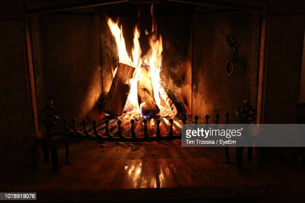 burning fireplace in darkroom at night - fireplace stock pictures, royalty-free photos & images