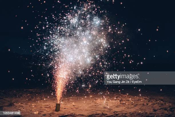 burning firework at beach during night - firework display stock pictures, royalty-free photos & images