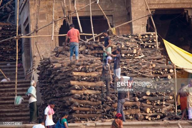 バラナシの川ガンジス川のほとりに森をストックするガーツの男を燃やす - fotofojanini ストックフォトと画像