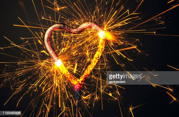 burning heart sparkler macro - heartburn stock photos and pictures