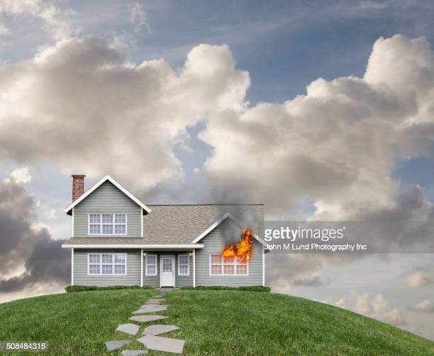 Burning house on grassy hill