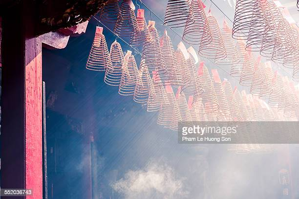 burning incense coils in an ancient pagoda - incense coils stock photos and pictures