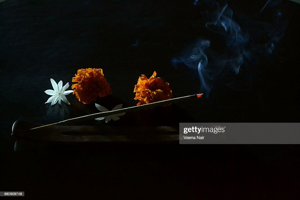 Burning incense sticks on a wooden incense holder and flowers : Stock Photo