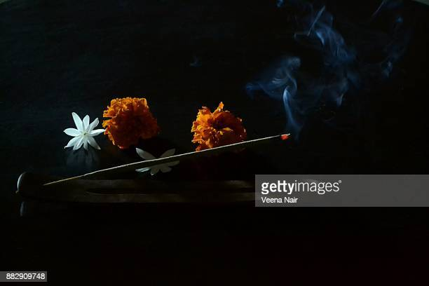 burning incense sticks on a wooden incense holder and flowers - incense stock photos and pictures