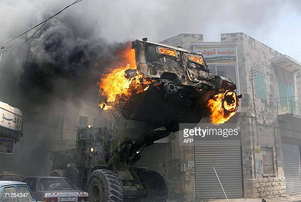 A burning Israeli military jeep is lifted by a forklift truck following clashes between Palestinians and Israeli soldiers in the West Bank city of...
