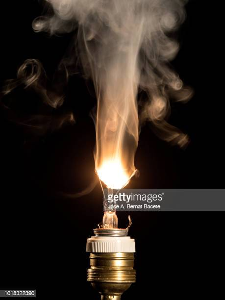 burning light bulb filament on a black background. - smoking crack stock photos and pictures