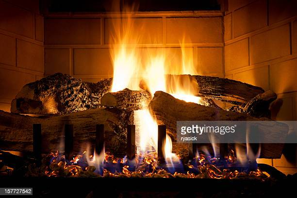 burning logs and glowing embers in gas fireplace - warming up stock pictures, royalty-free photos & images