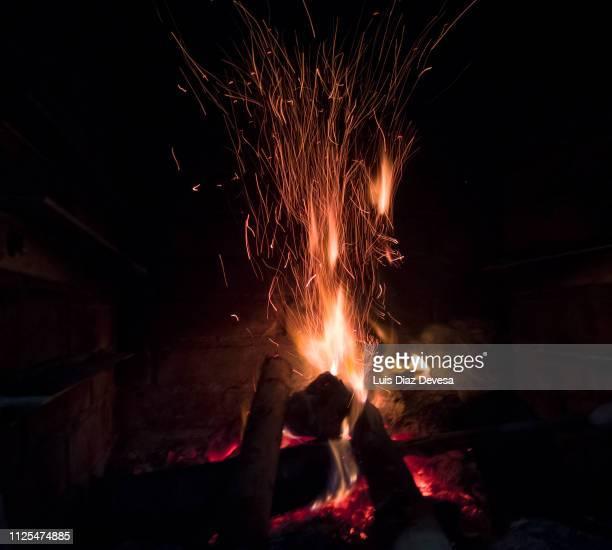 burning logs in a cozy fireplace - fuego al aire libre fotografías e imágenes de stock
