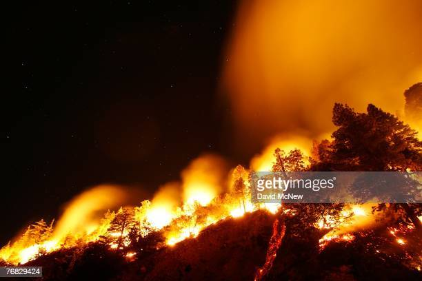 Burning logs roll down a hill as the Butler 2 Fire burns through the early morning hours on September 18, 2007 near Fawnskin, California. Earlier...