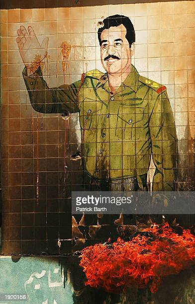 A burning mural of Saddam Hussein in Kirkuk April 11 2003 as looters ransack the city Kirkuk has fallen into chaos as the US 173rd Airborne division...