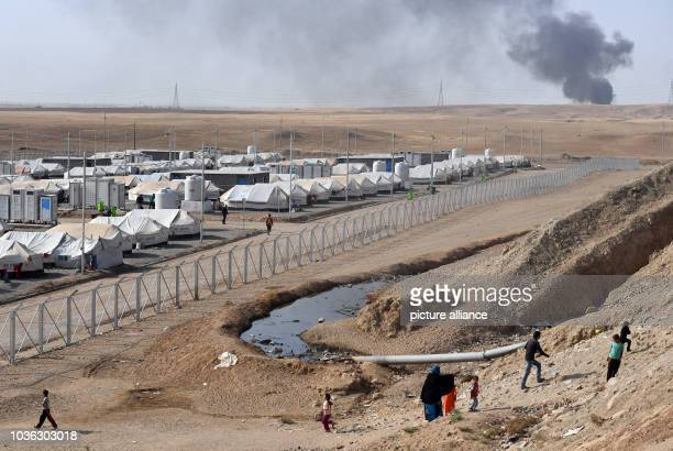 A burning oil facility can be seen behind the refugee camp Debaga between Erbil and Mossul Iraq 18 October 2016 The UN Refugee Relief Organisation...